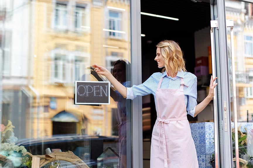 young business woman hanging open sign outside of business